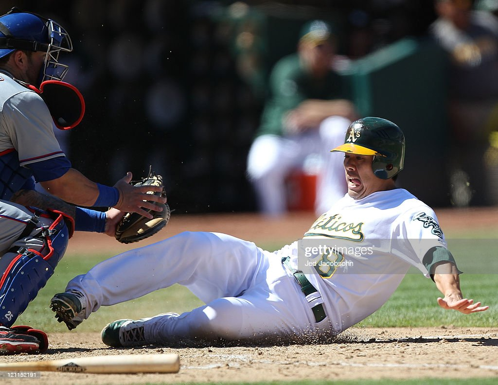 <a gi-track='captionPersonalityLinkClicked' href=/galleries/search?phrase=Kurt+Suzuki&family=editorial&specificpeople=682702 ng-click='$event.stopPropagation()'>Kurt Suzuki</a> #8 of the Oakland Athletics scores past <a gi-track='captionPersonalityLinkClicked' href=/galleries/search?phrase=Mike+Napoli&family=editorial&specificpeople=525007 ng-click='$event.stopPropagation()'>Mike Napoli</a> #25 of the Texas Rangers on a double by Brandon Allen at O.co Coliseum on August 14, 2011 in Oakland, California.