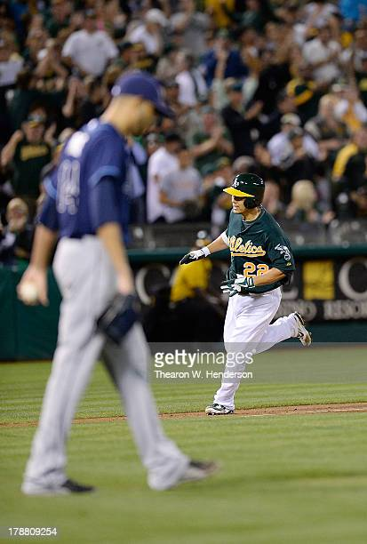 Kurt Suzuki of the Oakland Athletics trots around the bases after hitting a threerun home run as pitcher David Price of the Tampa Bay Rays walks back...