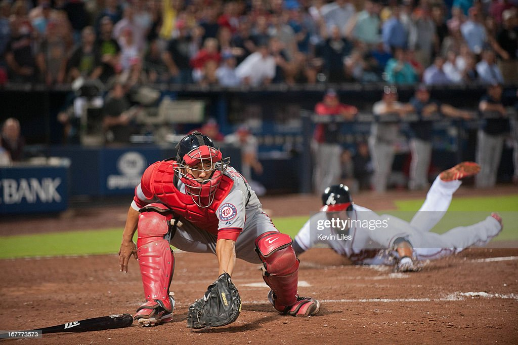 <a gi-track='captionPersonalityLinkClicked' href=/galleries/search?phrase=Kurt+Suzuki&family=editorial&specificpeople=682702 ng-click='$event.stopPropagation()'>Kurt Suzuki</a> #24 of the Washington Nationals fields the ball as <a gi-track='captionPersonalityLinkClicked' href=/galleries/search?phrase=Gerald+Laird&family=editorial&specificpeople=228949 ng-click='$event.stopPropagation()'>Gerald Laird</a> #11 of the Atlanta Braves scores during the 7th inning at Turner Field on April 29, 2013 in Atlanta, Georgia. The Braves defeated the Nationals 3-2.