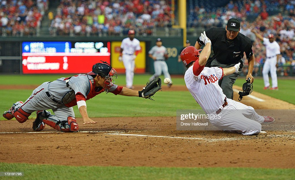 <a gi-track='captionPersonalityLinkClicked' href=/galleries/search?phrase=Kurt+Suzuki&family=editorial&specificpeople=682702 ng-click='$event.stopPropagation()'>Kurt Suzuki</a> #24 of the Washington Nationals is unable to make the tag on <a gi-track='captionPersonalityLinkClicked' href=/galleries/search?phrase=Chase+Utley&family=editorial&specificpeople=161391 ng-click='$event.stopPropagation()'>Chase Utley</a> #26 of the Philadelphia Phillies as he scores a run in the fourth inning on a hit by Domonic Brown #9 at Citizens Bank Park on July 9, 2013 in Philadelphia, Pennsylvania.
