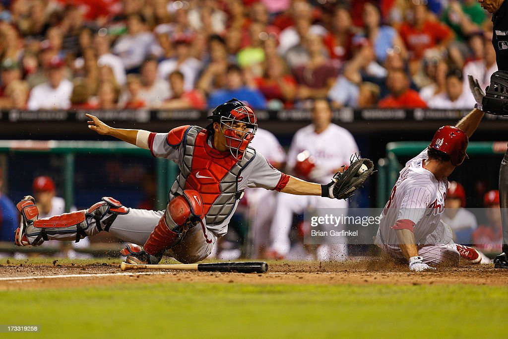 <a gi-track='captionPersonalityLinkClicked' href=/galleries/search?phrase=Kurt+Suzuki&family=editorial&specificpeople=682702 ng-click='$event.stopPropagation()'>Kurt Suzuki</a> #24 of the Washington Nationals reaches for Chase Utley #26 of the Philadelphia Phillies as he scores a run in the eighth inning of the game at Citizens Bank Park on July 11, 2013 in Philadelphia, Pennsylvania. Phillies won 3-1.