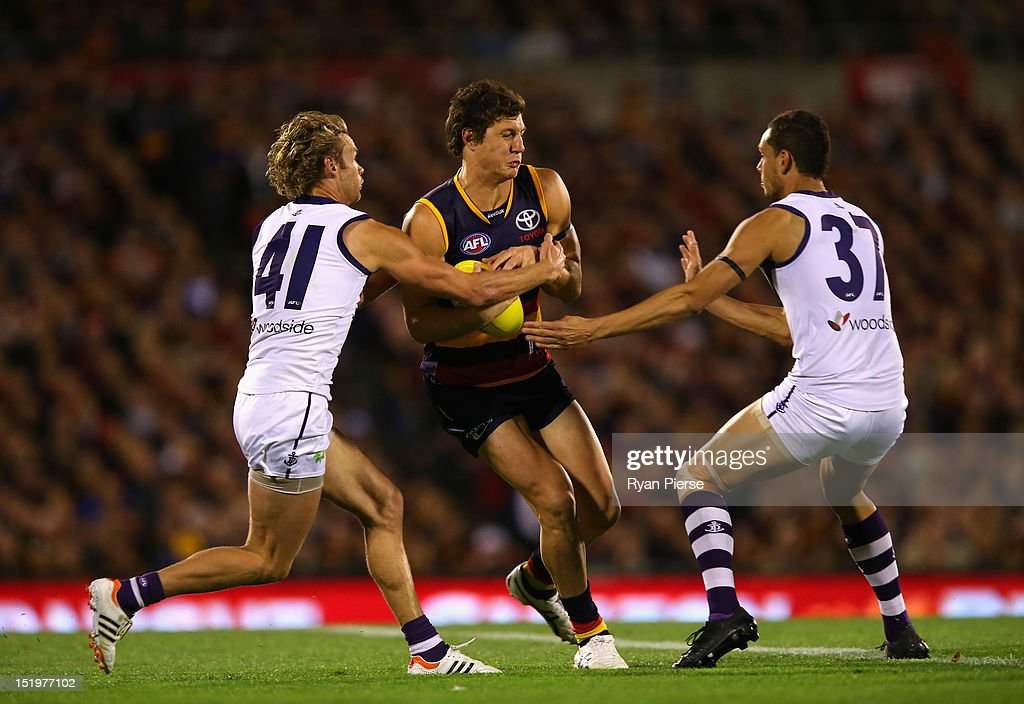 Kurt Tippett of the Crows is tackled by Paul Duffield of the Dockers and Michael Johnson of the Dockers during the AFL Second Semi Final match between the Adelaide Crows and the Fremantle Dockers at AAMI Stadium on September 14, 2012 in Adelaide, Australia.