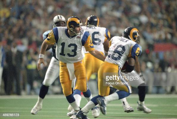 Kurt Warner of St Louis Rams turns to hand the ball off to Marshall Faulk against the Tennessee Titans during Super Bowl XXXIV at the Georgia Dome on...