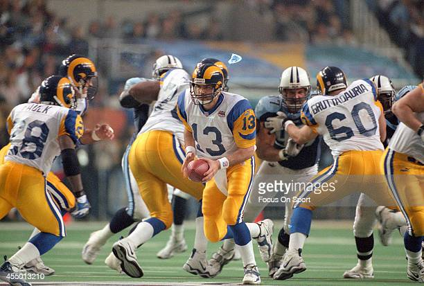 Kurt Warner of St Louis Rams turns to hand the ball to Marshall Faulk against the Tennessee Titans during Super Bowl XXXIV at the Georgia Dome on...