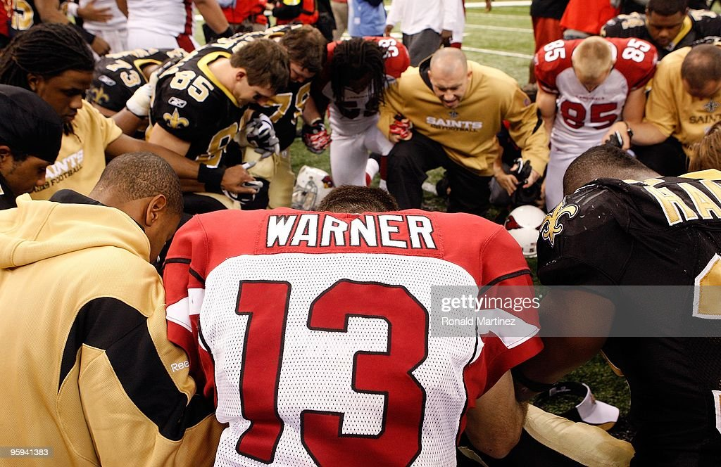 <a gi-track='captionPersonalityLinkClicked' href=/galleries/search?phrase=Kurt+Warner&family=editorial&specificpeople=202571 ng-click='$event.stopPropagation()'>Kurt Warner</a> #13 of the Arizona Cardinals kneels and prays with players from both the Cardinals and the New Orleans Saints after the Saints won 45-14 during the NFC Divisional Playoff Game at Louisana Superdome on January 16, 2010 in New Orleans, Louisiana.