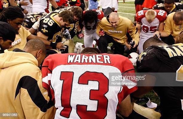 Kurt Warner of the Arizona Cardinals kneels and prays with players from both the Cardinals and the New Orleans Saints after the Saints won 4514...