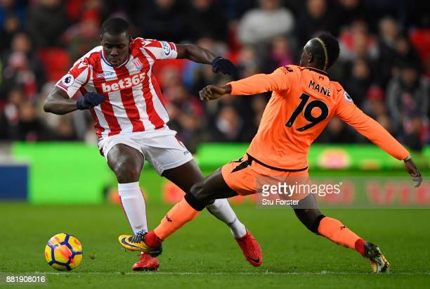 Kurt Zouma of Stoke City is challenged by Sadio Mane of Liverpool during the Premier League match between Stoke City and Liverpool at Bet365 Stadium...