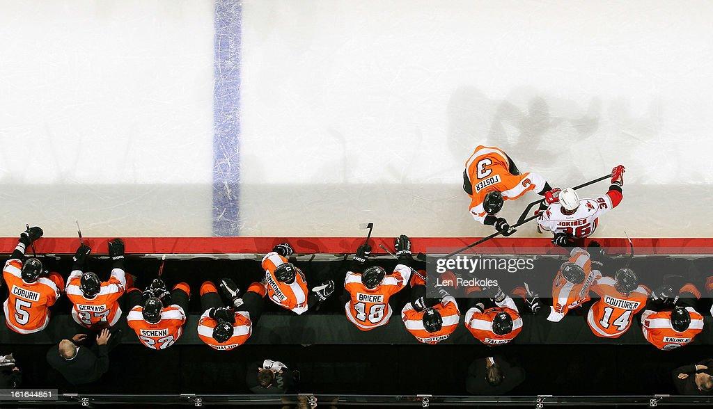 Kurtis Foster #3 of the Philadelphia Flyers checks Jussi Jokinen #36 of the Carolina Hurricanes into the bench on February 9, 2013 at the Wells Fargo Center in Philadelphia, Pennsylvania.