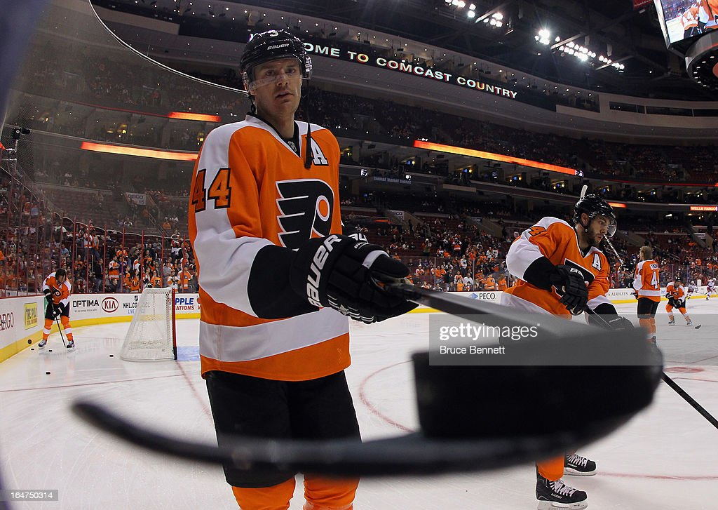 Kurtis Foster of the Philadelphia Flyers passes a puck through a hole to a fan during warmups prior to the game against the New York Rangers at the...