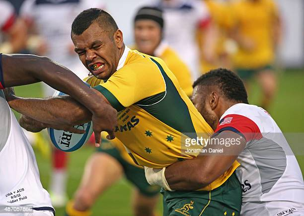 Kurtley Beale of the Australia Wallabies tries to fight his way between two United States Eagles players during a match at Soldier Field on September...