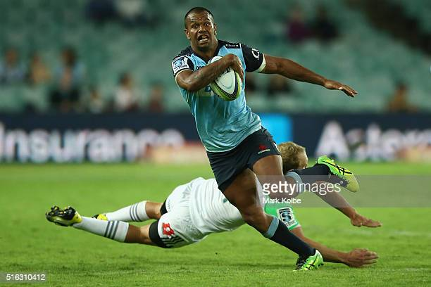 Kurtley Beale of the Waratahs beats the tackle of Matt Faddes of the Highlanders during the Super Rugby match between the New South Wales Waratahs...