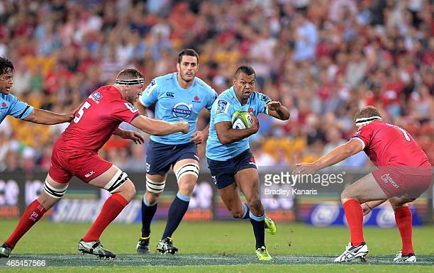 Kurtley Beale of the Waratahs breaks through the defensive line during the round 4 Super Rugby match between the Queensland Reds and the New South...