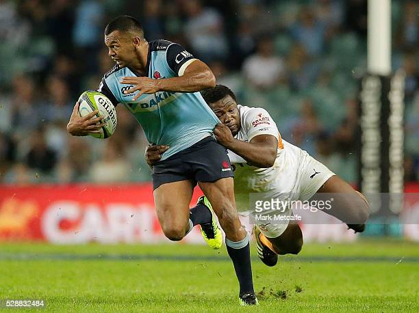 Kurtley Beale of the Waratahs is tackled by Teboho Mohoje of the Cheetahs during the round 11 Super Rugby match between the Waratahs and the Cheetahs...