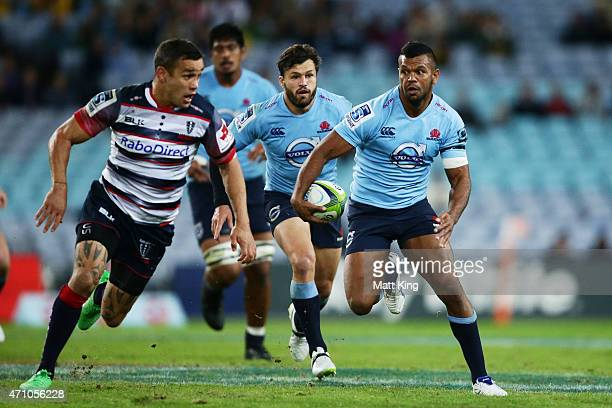 Kurtley Beale of the Waratahs takes on the defence during the round 11 Super Rugby match between the Waratahs and the Rebels at ANZ Stadium on April...