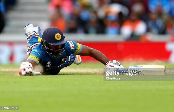 Kusal Perera of Sri Lanka dives to make his ground and injures himself in the process during the ICC Champions trophy cricket match between India and...