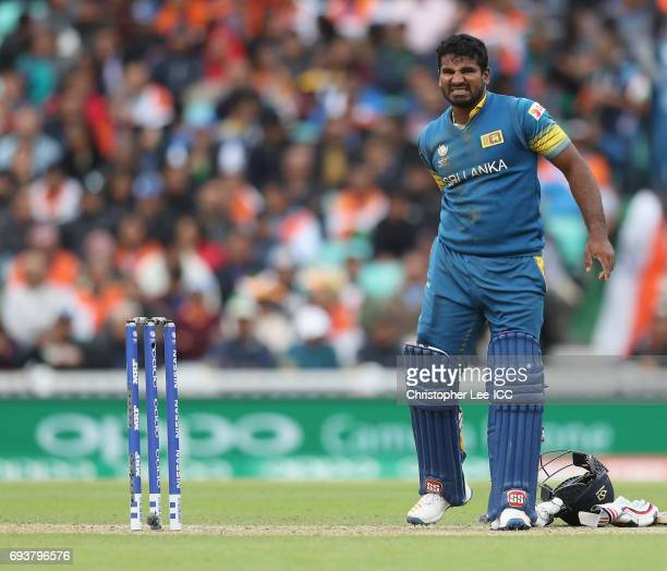 Kusal Perera of Sri Lanka holds the back of his thigh after picking up and injury during the ICC Champions Trophy Group B match between India and Sri...