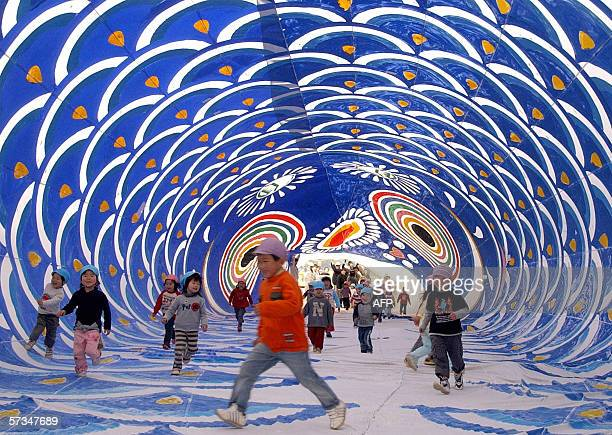 Children play inside a huge carpshaped streamer in the town of Kusu western Japan 17 April 2006 The carpshaped streamer was 50 meters long and 20...