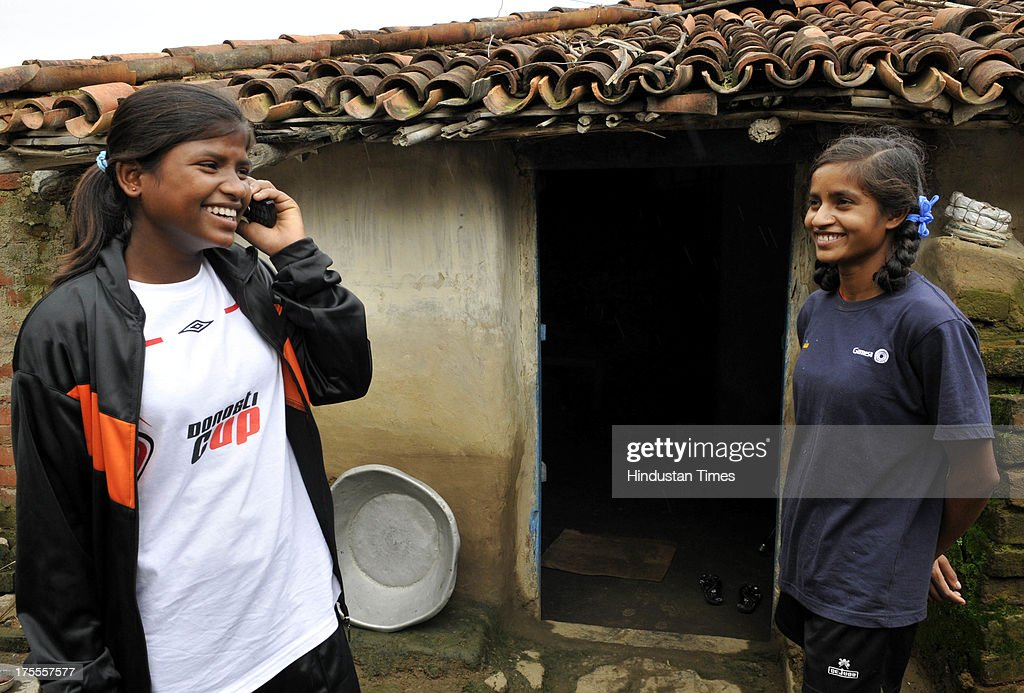 Kusum Kumari (L) and Rinki Kumari of the Yuwa Football Academy talks to cell phone at Hutap village on August 2, 2013 in Ranchi, India. On July 13, the 18 tribal girls representing Yuwa India under-14 all-girls team were placed third among 10 teams playing for the Gasteiz Cup in Victoria Gasteiz in Spain. In 2012, Yuwa became the first organisation in India to win the Nike Gamechangers Award. Yuwa also won the NDTV Spirit of Sports Award, Times Now Amazing Indians Award. Set up in 2009 by Franz Gastler, its an NGO that uses football to combat child marriage and human trafficking in Jharkhands tribal belt. Gastler, a US citizen, started as an English teacher for underprivileged children when he was requested by the girls to teach them football. He formed Yuwa India, a U-14 side with girls from local villages. Having started with 15 girls in 2009, Yuwa now has over 200 aspiring footballers. The Jharkhand government has announced it would build a stateof-the-art stadium on five acres of land for the Yuwa girls. Chief Minister Hemant Soren also announced cash awards of Rs 21,000 to each of the 18 girls who were in the squad. The Yuwa team would be felicitated by the state government on August 29, the National Sports Day.