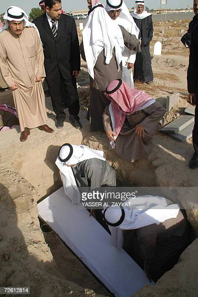 Kuwaiti mourners bury the coffin of one of three Kuwaitis found recently in a mass grave in Iraq during a funeral 21 November 2006 at a cemetary in...