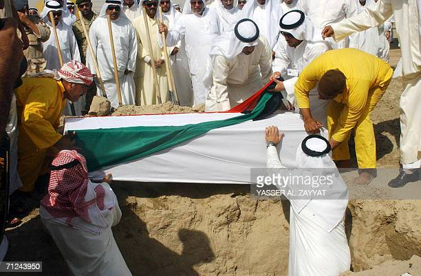 Reletives bury the coffin of one of three Kuwaitis found recently in a mass grave in Iraq during a funeral 20 June 2006 at a cemetary in Kuwait City...