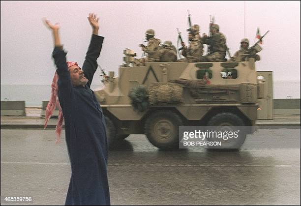 A Kuwaiti citizen raises his arms in celebration as a Saudi personnel carrier passes on the street 27 February 1991 after allied forces rolled into...