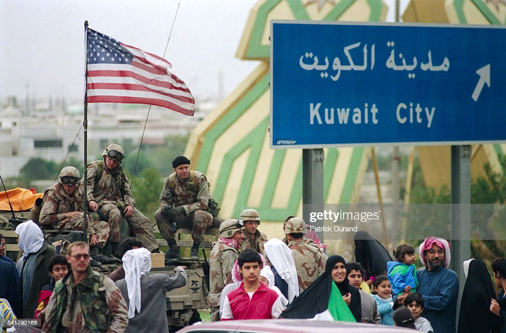 Kuwaiti citizens and US Marines gather near a road sign after the liberation of Kuwait City during the Persian Gulf War In August of 1990 Iraqi...