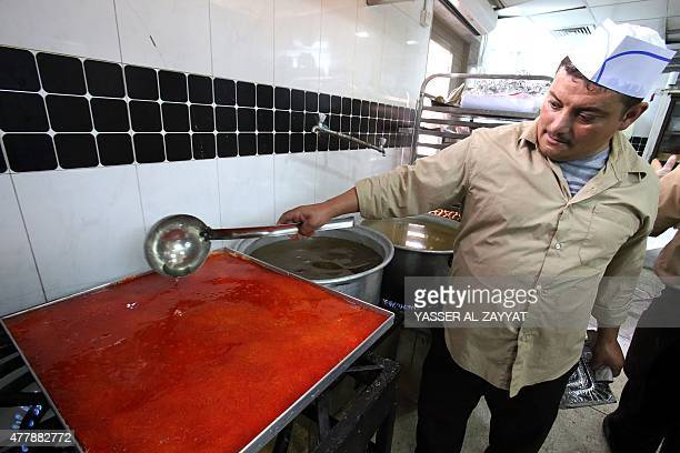 A Kuwaiti employee prepares a traditional Arab sweet known as Kanafa at a sweets shop during the Muslim fasting month of Ramadan on June 20 in Kuwait...