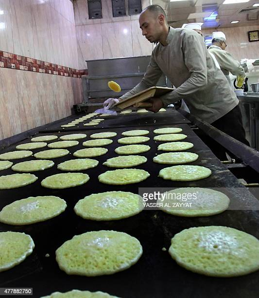 A Kuwaiti employee prepares traditional Arab pancakes known as Qatayef at a sweets shop during the Muslim fasting month of Ramadan on June 20 in...