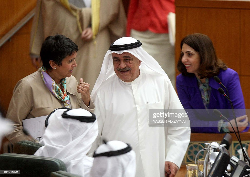 Kuwaiti Finance Minister Mustafa al-Shamali (C) speaks with Kuwaiti MP Safaa al-Hashem (L) and Kuwaiti Minister of Planning and Development Rola Dashti (R) during a parliament session at the Kuwait national assembly in Kuwait City on March 19, 2013. Kuwait's parliament passed in principle a bill that requires the government to buy billions of dollars of bank loans owed by citizens and reschedule them after waiving interest. AFP PHOTO / YASSER AL-ZAYYAT