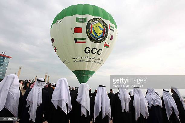 Kuwaiti folcloric dancers perform as an Emirati team flies a hot air balloon that bears the logo of the Gulf Cooperation Council in front of the...