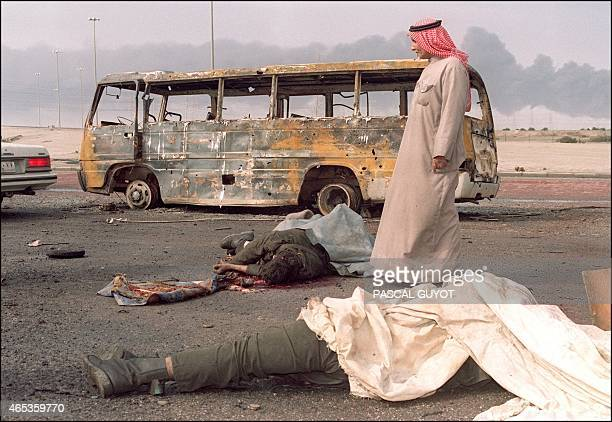 A Kuwaiti looks 27 February 1991 in Kuwait City at the bodies of Iraqis killed during fighting between allied forces and Iraqi army in a suburb of...