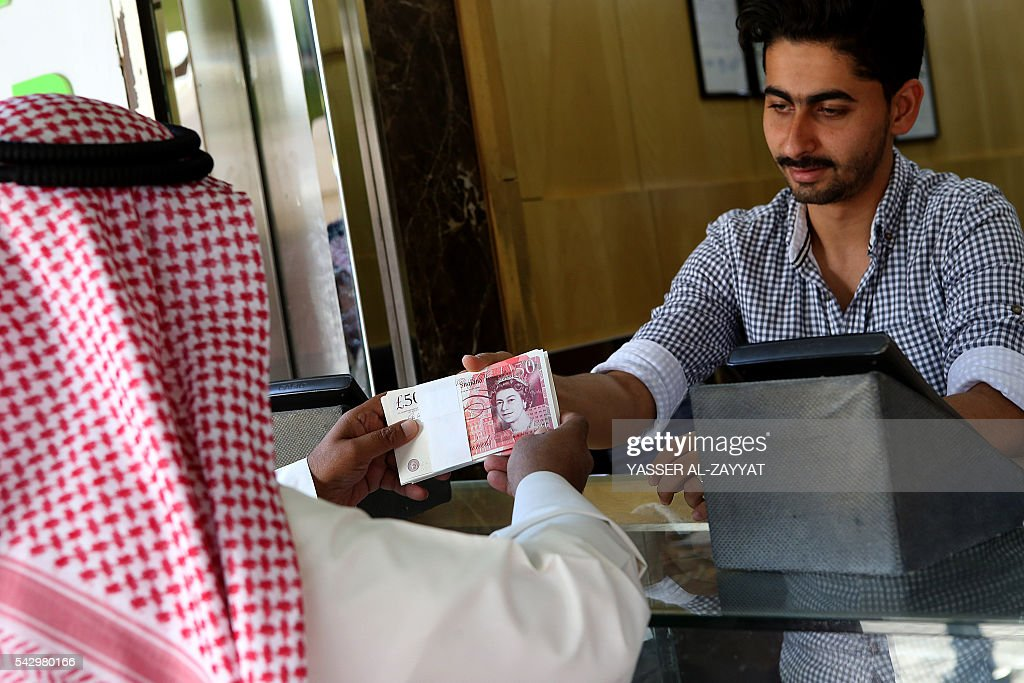 A Kuwaiti man buys British Pounds at a money exchange shop in Kuwait City on June 25, 2016. The British Pound has plunged to its lowest rate since 1985 after the United Kingdom's vote to exit from the European Union. / AFP / YASSER