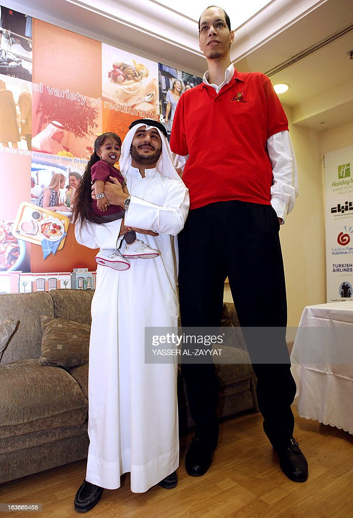 A Kuwaiti man carries Indian <a gi-track='captionPersonalityLinkClicked' href=/galleries/search?phrase=Jyoti+Amge&family=editorial&specificpeople=6359264 ng-click='$event.stopPropagation()'>Jyoti Amge</a>, 19, the world's shortest woman next to Morocco's Brahim Takioullah, who has the largest feet in the world according to the Guinness Book of Records, during an event in Kuwait City, on March 14, 2013. Amge and Takioullah are in Kuwait as part of a children's one-minute competition organized by the Guinness Book of Records. AFP PHOTO/YASSER AL-ZAYYAT