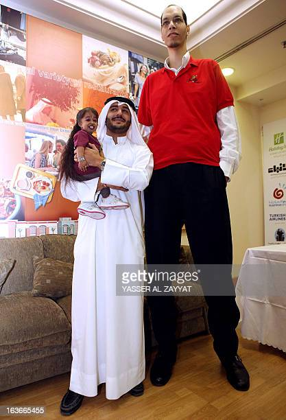 A Kuwaiti man carries Indian Jyoti Amge the world's shortest woman next to Morocco's Brahim Takioullah who has the largest feet in the world...