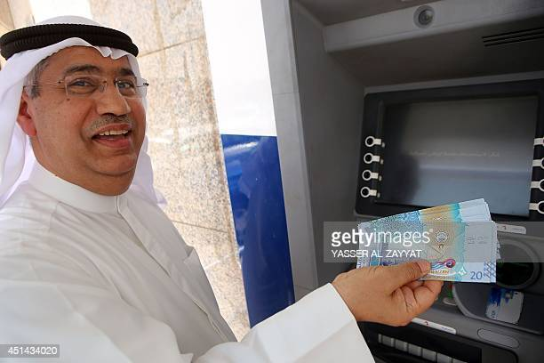 A Kuwaiti man holds up the the sixth edition of a 20 Kuwaiti Dinar bill that was recently put into circulation by the Central Bank next to an ATM in...