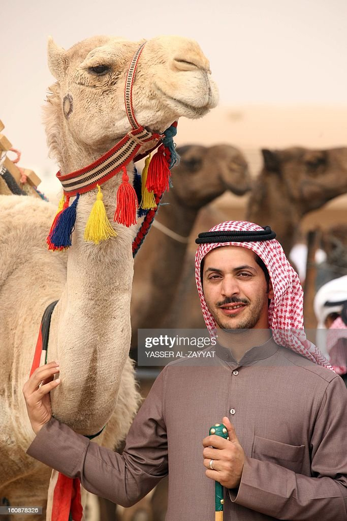 A Kuwaiti man poses near camels part during a competition in al-Salmi district, 120 kms west of Kuwait City on February 7, 2013, held as part of the ongoing Popular Heritage Festival. The one-month event is held annually to commemorate popular activities in Kuwaiti heritage, featuring camel races, falcons contests, fishing competitions and others.