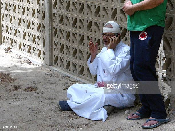 A Kuwaiti man with bloodstained clothes and a bandaged head uses a phone at the site of a suicide bombing that targeted the Shiite AlImam alSadeq...