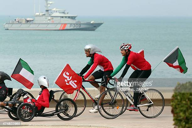 Kuwaiti men wearing clothes in their national colours ride bicycles on February 25 2014 during celebrations to mark the oilrich Gulf emirate's 53rd...