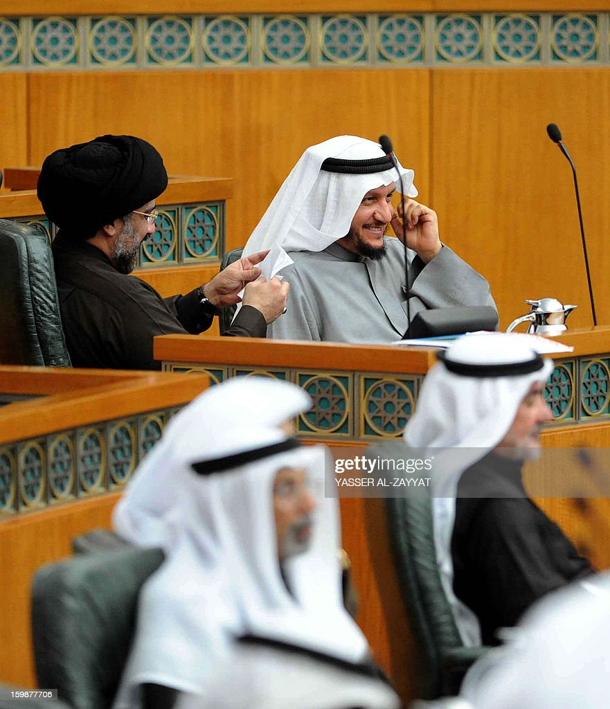 Kuwaiti Minister of Justice and Islamic Affairs Sharida al-Meosharji (R) shares a laugh with Kuwaiti Shiite MP Hussein al-Qallaf during a parliament session at the National Assembly in Kuwait City on January 22, 2013. Kuwait MPs overwhelmingly ratified a settlement deal between the Kuwaiti and Iraqi national carriers under which Baghdad will pay $500 million in compensation, ending a 22-year-old dispute.