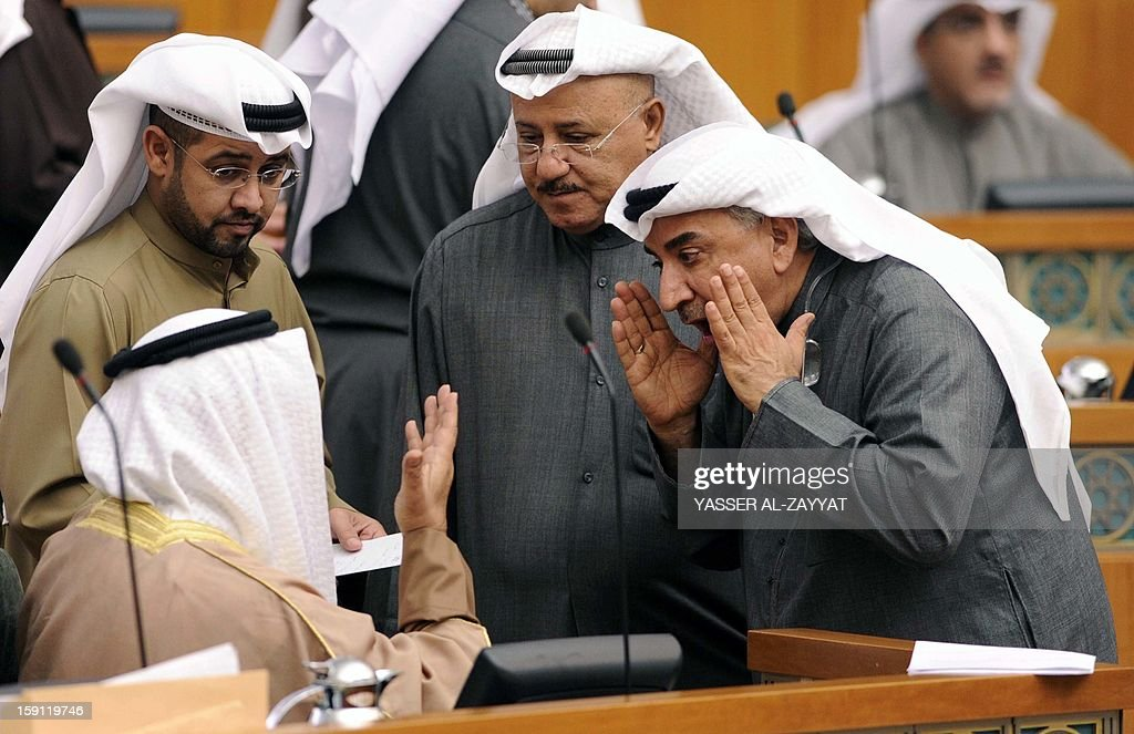 Kuwaiti MPs AbdulHameed Dashti (R), Nabeel al-Fadhel (C) and Hisham al-Baghli, talk to Kuwaiti Prime Minister Sheikh Jaber al-Mubarak al-Sabah (sitting) during a parliament session at Kuwait National Assembly in Kuwait City on January 8, 2013. Kuwait parliament overwhelmingly approved the controversial electoral decree that caused the opposition in the oil-rich Gulf state to boycott the December 1 general elections.