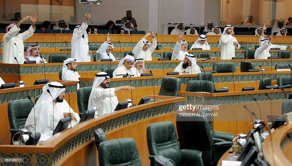 Kuwaiti MPs take part in a parliament session at Kuwait national assembly in Kuwait City on March 20,2013. Kuwait's parliament passed in principle a bill that requires the government to buy billions of dollars of bank loans owed by citizens and reschedule them after waiving interest.