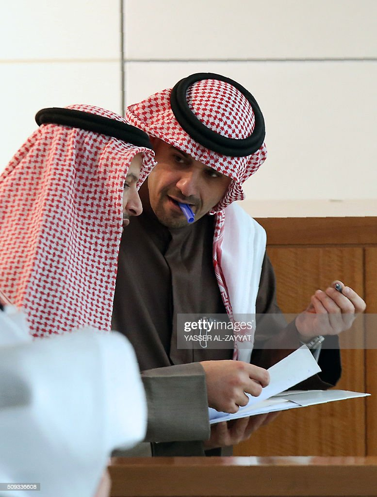 Kuwaiti Oil and Finance Minister Anas al-Saleh (R) talks with Kuwaiti Member of Parliament Talal al-Shale during a parliament session, at Kuwait's National Assembly in Kuwait City on February 10, 2016. / AFP / YASSER AL-ZAYYAT