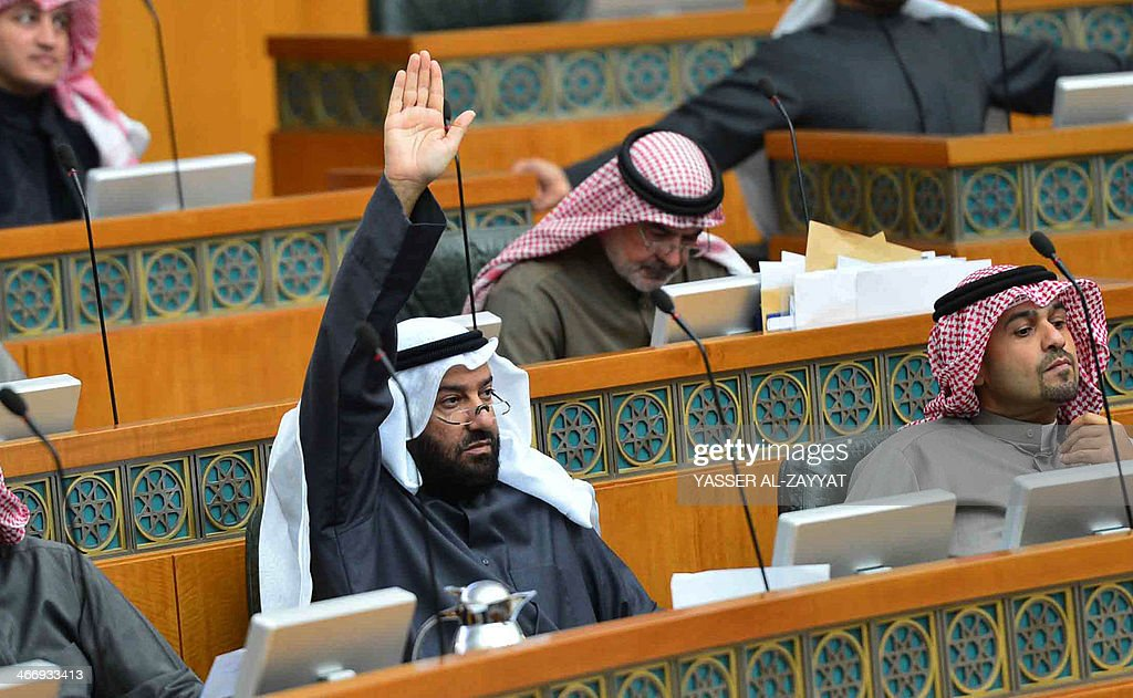 Kuwaiti Oil minister Ali al-Omair (L), raises his hand during a parliament session at Kuwait's national assembly in Kuwiat City on February 5,2014. al-Omair said today that if oil workers carry out a threat to go on strike, the OPEC member has a contingency plan to ensure that production is not disrupted.