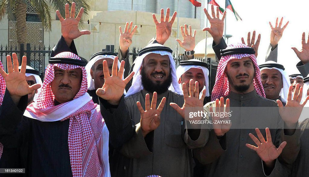 Kuwaiti opposition and former MPs Musallam al-Barrak (L) Falah al-Sawwagh (C) and Bader al-Dahum (R) along with supporters raise four fingers in reference to the four-votes system, as they leave the Palace of Justice in Kuwait City on February 10, 2013. AFP PHOTO/YASSER AL-ZAYYAT