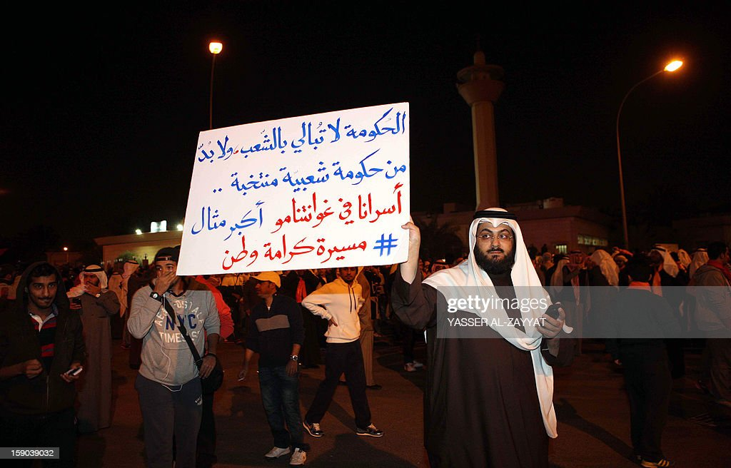 A Kuwaiti opposition protestor holds an anti-government placard as he takes part in a demonstration demanding that the new parliament be dissolved and controversial legislation be scrapped in Kuwait City on January 6, 2013. Kuwaiti riot police fired tear gas and stun grenades at hundreds of the demonstrators and arrested several including Osama al-Shaheen, a member of the previous opposition-dominated parliament. AFP PHOTO / YASSER AL ZAYYET