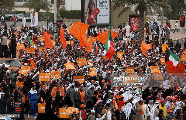 Kuwaiti opposition supporters waving Kuwaiti and orange flags march on a major road in Kuwait City on December 8 during a demonstration to demand...