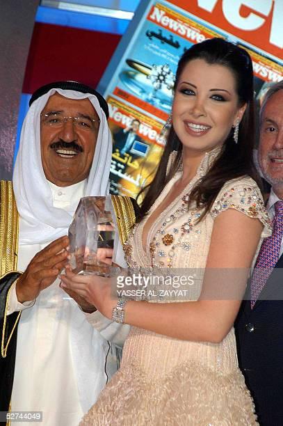 Kuwaiti Prime Minister Sheikh Sabah alAhmad alSabah presents an award to Lebanese singer Nancy Ajram who was chosen by Newsweek's Arabic edition as...
