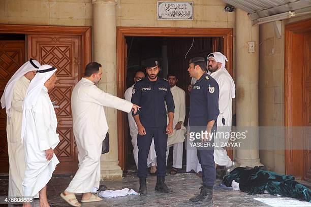 Kuwaiti security forces stand next to a body wrapped in shrouds as they inspect the site of a suicide bombing that targeted the Shiite AlImam alSadeq...