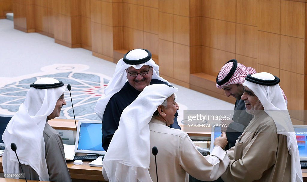 Kuwaiti Shiite MPs Adnan Abdulsamad, Abdulhameed Dashti and Ahmad Lari talk with Kuwaiti Housing Minister Yasser Abul (R) and Minister of Communications Essa al-Kandari during a parliament session on February 9, 2016 at the national assembly in Kuwait City. / AFP / YASSER AL-ZAYYAT