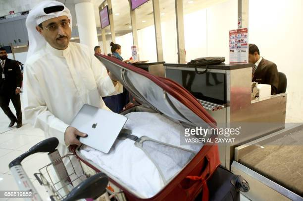 Kuwaiti social media activist Thamer alDakheel Bourashed puts his laptop inside his suitcase at Kuwait International Airport in Kuwait City before...